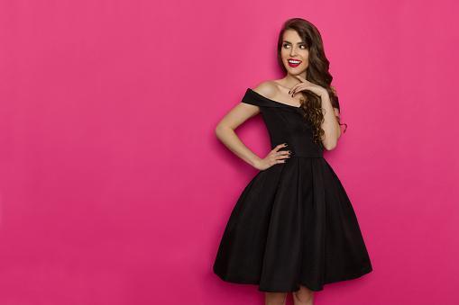 стоит красивая девушка в черном вечернем платье с пышной юбкой