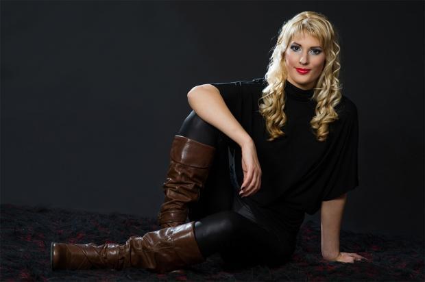 блондинка с длинными волосами сидит на полу в темной одежде и высоких коричневых сапогах