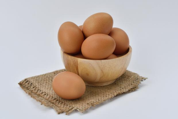 куриные яйца в глиняной мисочке, стоящей на салфетке