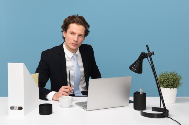 Мужчина в костюме сидит за рабочим столом