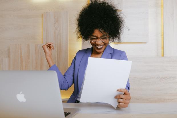 Девушка в сиреневой блузе держит в руках листок бумаги и улыбается