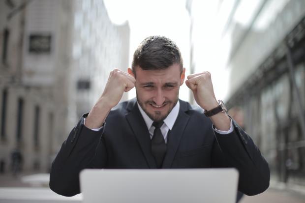 Молодой мужчина в костюме сидит перед компьютером