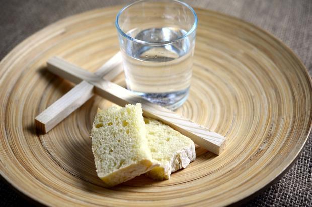 деревянные крест на блюде с водой и хлебом
