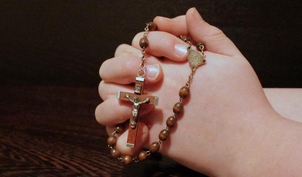 сложенные в молитве руки с четками