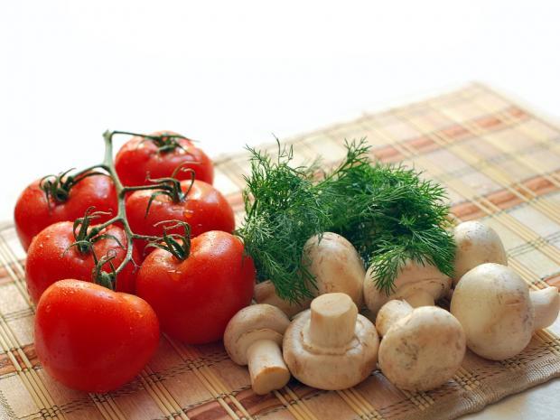 шампиньоны с красными помидорами и зеленью лежат на столе