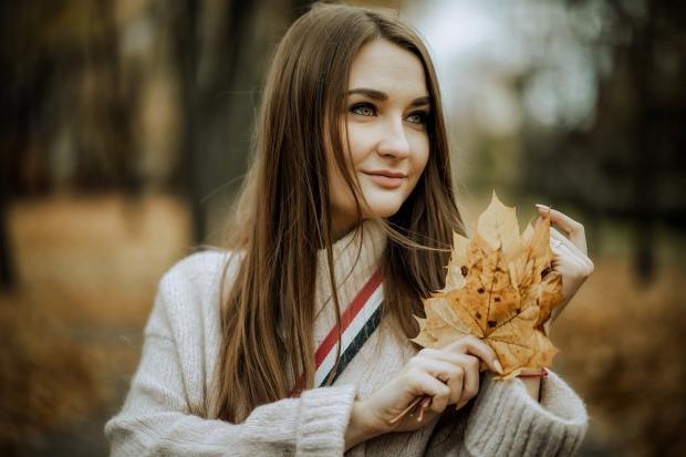женщина с распущенными волосами и теплом белом свитере держит в руках желтые кленовые листья