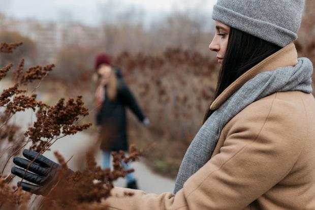 девушка в серой шапке и шарфе прикасается рукой в черной перчатки к засохшей осенней траве