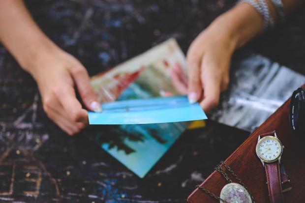 девушка пересматривает старые открытки из коробки