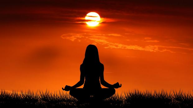 девушка медитирует на закате солнца
