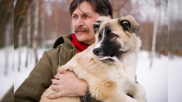 мужчина держит в руках собаку