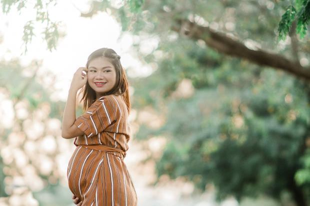 Беременная девушка в коричневом платье