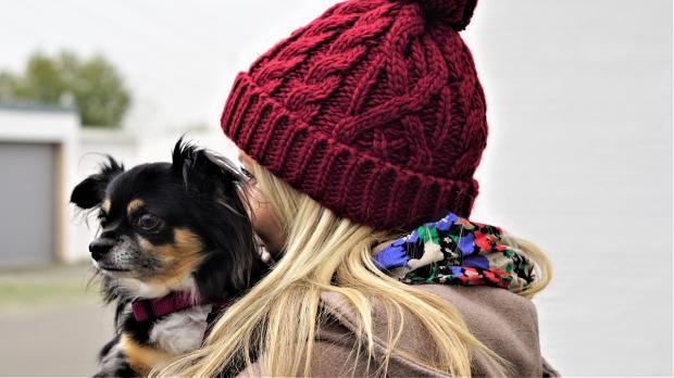 девушка в красной шапочке держит на руках маленькую собачку