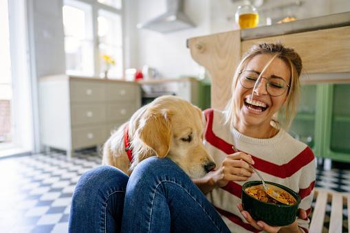 смеющаяся девушка кормит собаку с ложки
