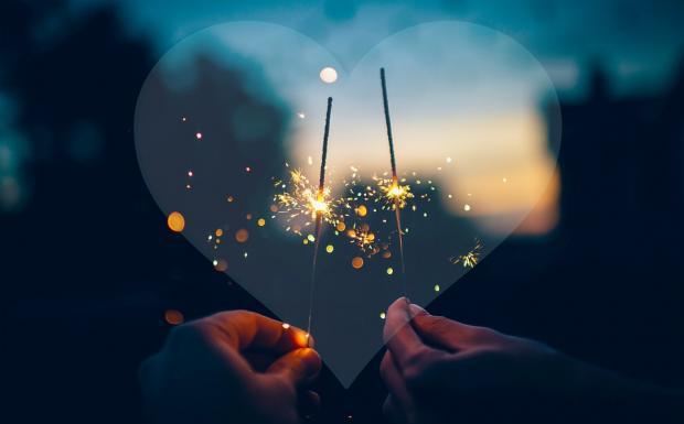две руки с зажженными бенгальскими свечами на фоне сердца