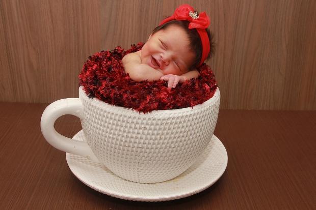 младенец с красным бантом в белой чайной чашке