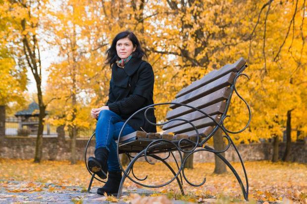 девушка сидит на красивой кованой скамейке в осеннем парке