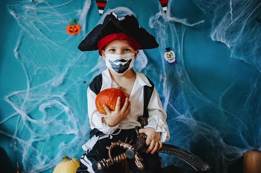 ребенок в костюме пирата с тыквой