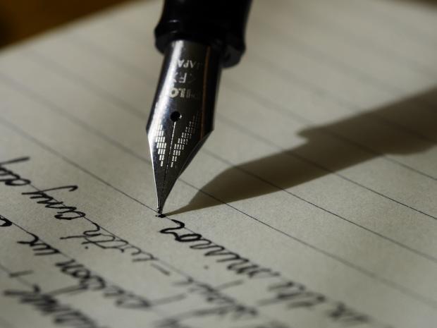 лист бумаги, перьевая ручка пишет
