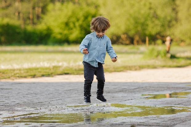 мальчик прыгает в луже