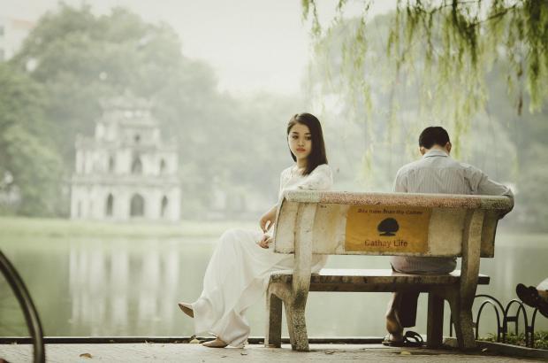 парень и девушка сидят на скамейке, отвернувшись друг от друга