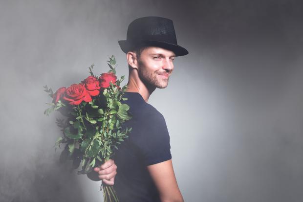 молодой человек в шляпе держит за спиной букет цветов