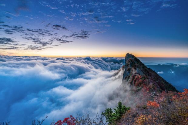 вершина горы, белые облака на голубом небе
