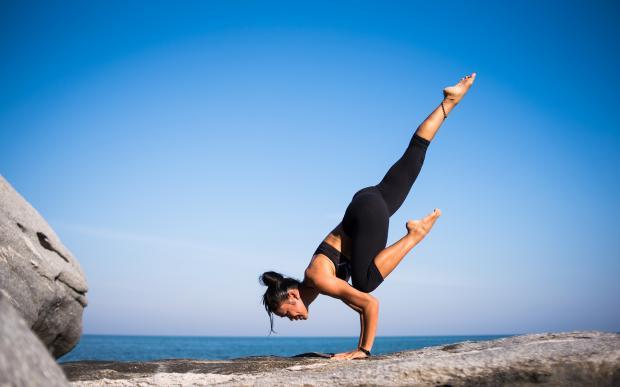девушка в одной из позиций йоги стоит на скале