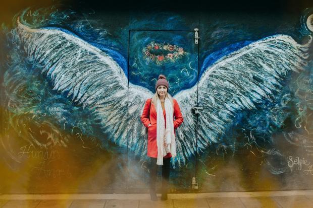 Девушка в красном пальто стоит на фоне изображения больших крыльев