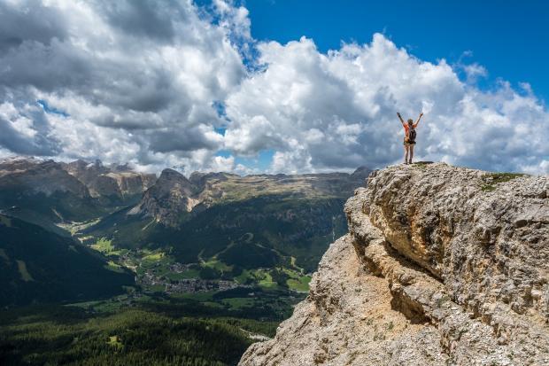 человек, раскинув руки, стоит на вершине горы