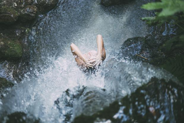 девушка стоит под струями водопада