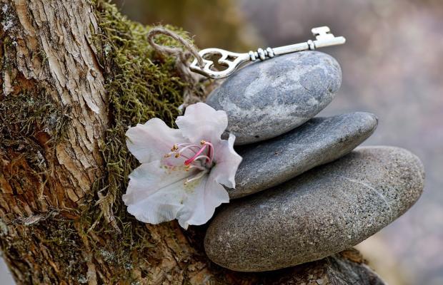 три камня лежащих друг на друге, на них ключ с цветком