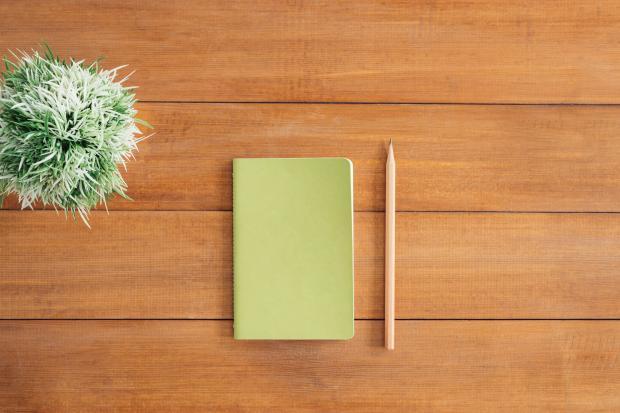 Зеленый блокнот и карандаш на столе