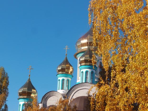 золоченые купола храма осенью рядом с березой