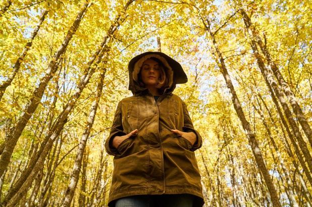 девушка в куртке с накинутым на голову капюшоном стоит среди желтого осеннего леса