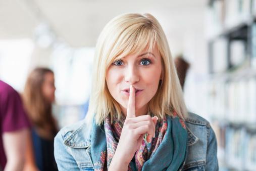 девушка держит палец у рта - молчание