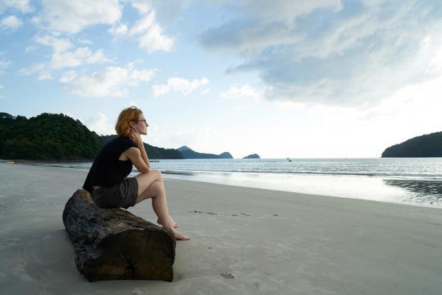 девушка сидит на берегу моря в задумчивости