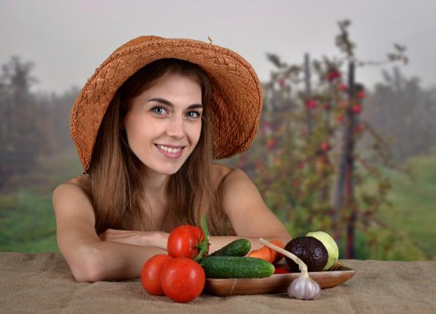 красивая девушка в шляпке перед разложенными на столе овощами