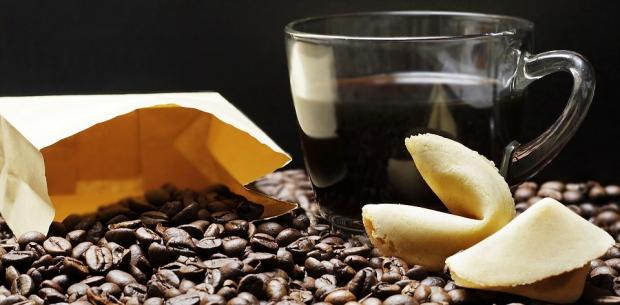 чашка кофе рядом с кофейными зернами россыпью