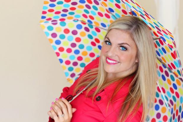 смеющаяся блондинка в красном платье под разноцветным зонтиком