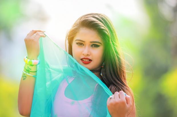 девушка держит в руках прозрачный бирюзовый шарфик