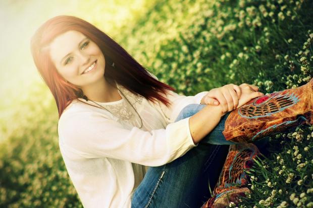 сидит на траве девушка в белом джемпере и синих джинсах