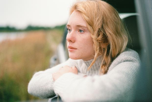 Блондинка с веснушками на лице в белом свитере выглядывает из окна машины