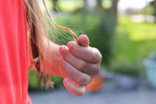 Рука девочки держит локон длинных волос