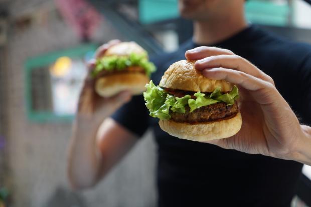 Молодой мужчина в черной футболке держит два гамбургера
