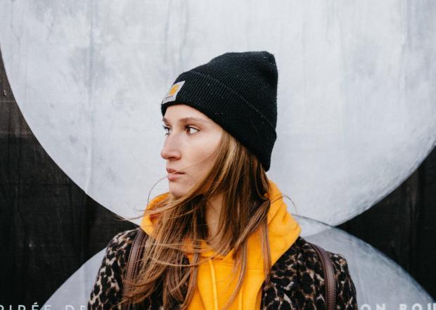 Девушка в желтом худи и черной шапке стоит у стены