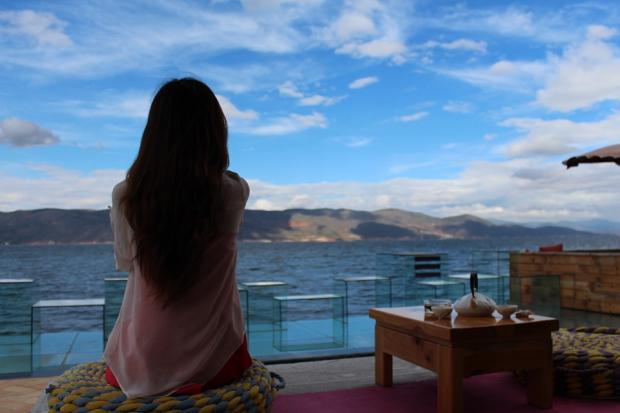 девушка на террасе сидит лицом к морю