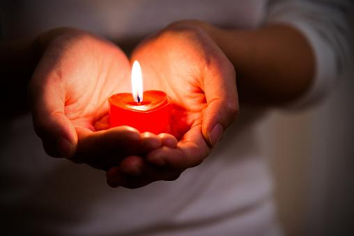 горящая свеча в соединенных ладонях