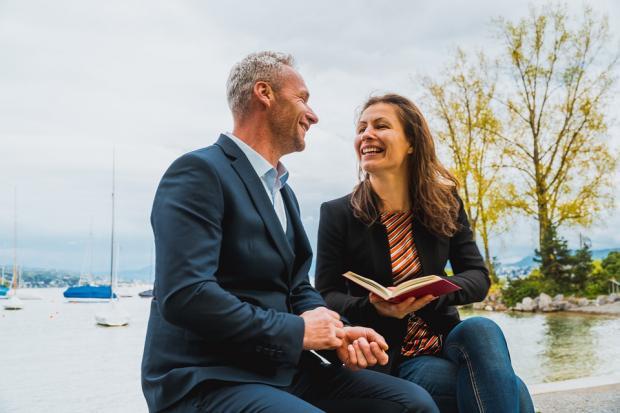 мужчина с девушкой обсуждают прочитанную книгу на скамейке
