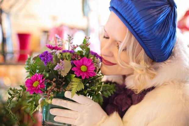 женщина нюхает букет цветов