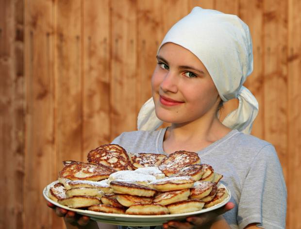 девушка в косынке держит блюдо с оладьями